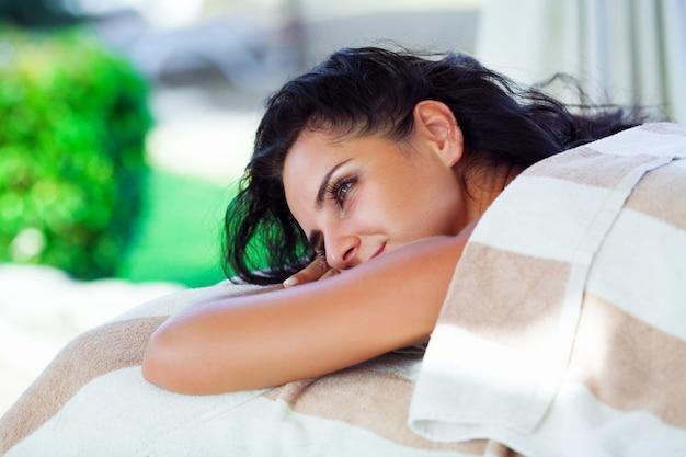 Spa-massage. nahaufnahme der schönen gesunden glücklichen lächelnden frau, die draußen im tagesbadekurortsalon sich entspannt. masseur handmassage hals mit aromatherapieöl. entspannen sie sich körperpflege-schönheits-behandlungs-konzept