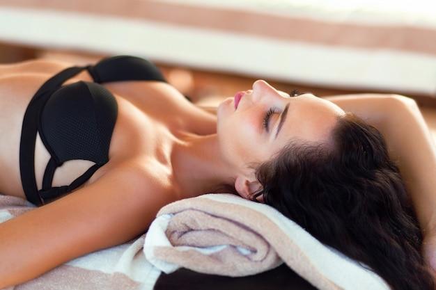 Spa-massage. nahaufnahme der schönen gesunden glücklichen lächelnden frau, die draußen im tagesbadekurortsalon sich entspannt.