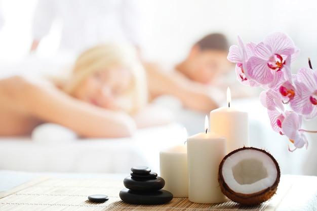 Spa-massagewerkzeuge und frauen, die massage auf hintergrund erhalten