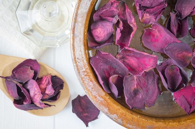 Spa mit schönen rosenblättern und einer tonschale.