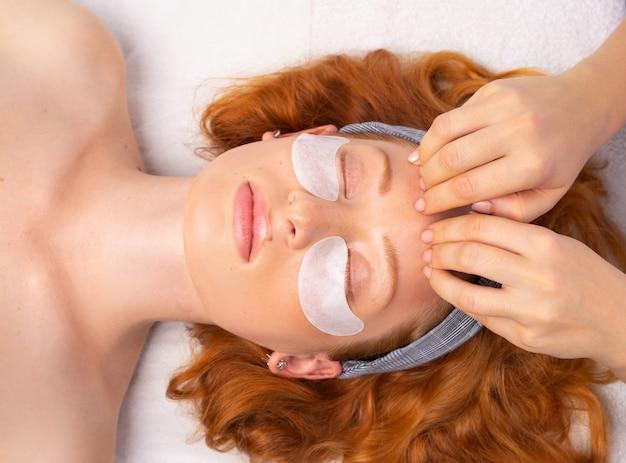 Spa. nach dem auftragen der transparenten maske führt die kosmetikerin eine gesichtsmassage durch. das konzept einer gesunden, feuchten und gepflegten haut.