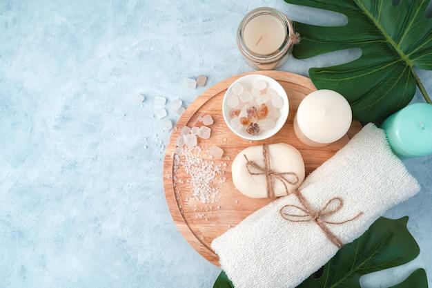 Spa-produkte, seife, handtuch, salz, kerzen auf hellblauem hintergrund mit tropischen blättern.