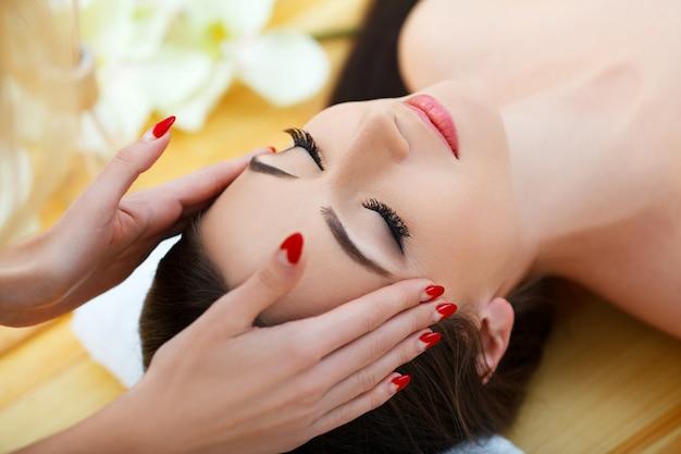 Spa-salon. junge frau, die auf einer massagetabelle, entspannend liegt.