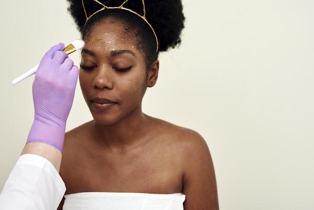 Spa schönheitsbehandlung, hautpflege. frau, die gesichtspflege durch kosmetikerin am spa-salon erhält. junge kosmetikerin, die gesichtsmaske durch bürste im spa anwendet.
