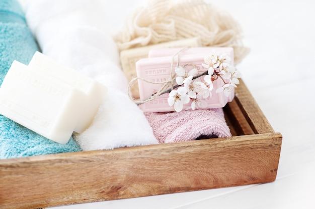 Spa seifenhintergrund. natürliche seife mit sakura-blumen und handtüchern auf einem holzkorb. bad ti
