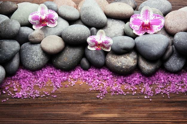 Spa-steine und orchidee auf holztisch