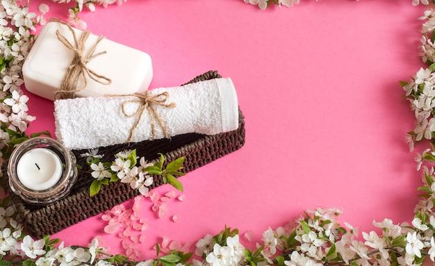 Spa stillleben auf isolierter rosa wand mit frühlingsblumen