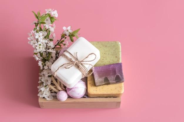 Spa stillleben auf rosa wand mit frühlingsblumen