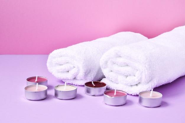 Spa stillleben behandlung mit kerzen und handtüchern auf rosa hintergrund, kopieren platz für text