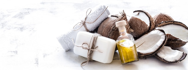 Spa stillleben der bio-kosmetik mit kokosnüssen auf einem hellen hölzernen hintergrund, körperpflegekonzept