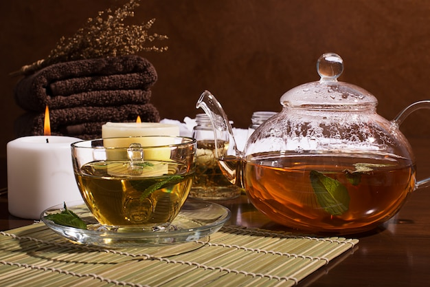 Spa-stillleben: grüner tee, aromaöl, handtücher