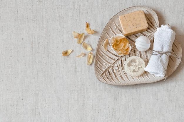 Spa stillleben mit badzubehör für die körperpflege unter blütenblättern draufsicht. gesundheits- und hygienekonzept.