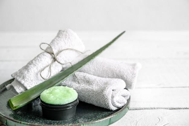 Spa-stillleben mit bio-hautpflege, frischem aloe-blatt und handtüchern. das konzept der schönheit und bio-kosmetik hintergrund