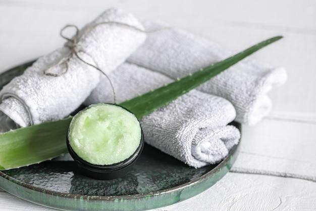 Spa-stillleben mit bio-hautpflege, frischem aloe-blatt und handtüchern. das konzept der schönheit und bio-kosmetik.