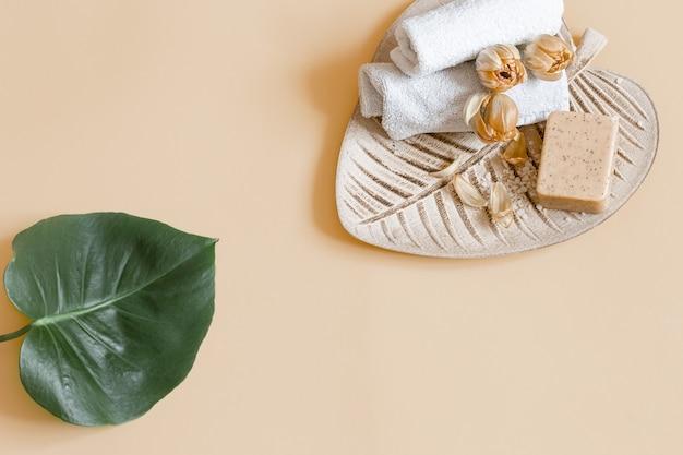 Spa stillleben mit blumen, seife und handtüchern. gesundheits- und schönheitskonzept.