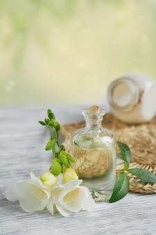 Spa-stillleben mit parfüm und aromaölflasche, umgeben von freesienblüten, auf heller oberfläche