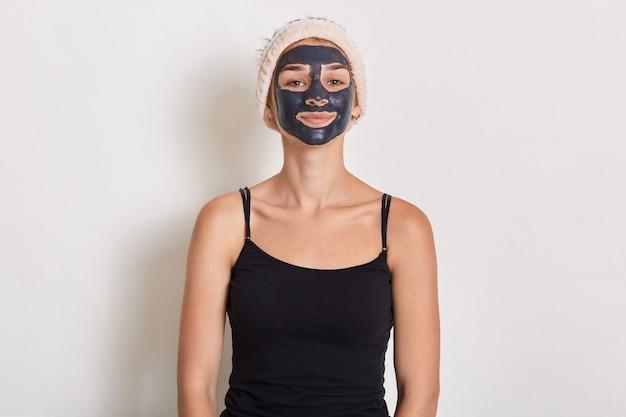 Spa teen frau, die schwarze gesichtslehmmaske anwendet. schönheitsbehandlungen zu hause