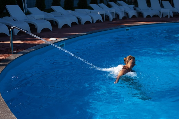 Spa-therapie eine ältere frau genießt eine rücken- und nackenmassage mit einem wasserstrahl im pool bei einem heißen...