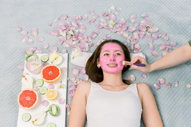 Spa-therapie für junge lächelnde frau, die gesichtsmaske im schönheitssalon erhält - drinnen. hübsches mädchen mit rosa gesichtsmaske auf gesicht, das auf bett, früchten und blumen um sie herum liegt