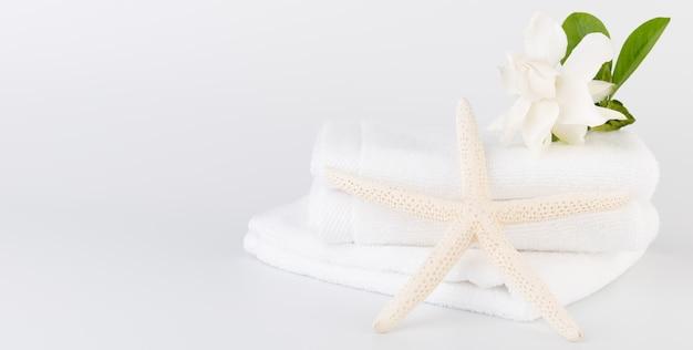 Spa- und gesundheitskonzepte einrichten mit stapel weißer handtücher sternfisch, gardenia blumen auf weißem hintergrund