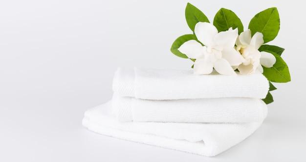 Spa- und gesundheitskonzepte mit einem stapel weißer handtücher und tropischer gardenia-blumen auf weiß