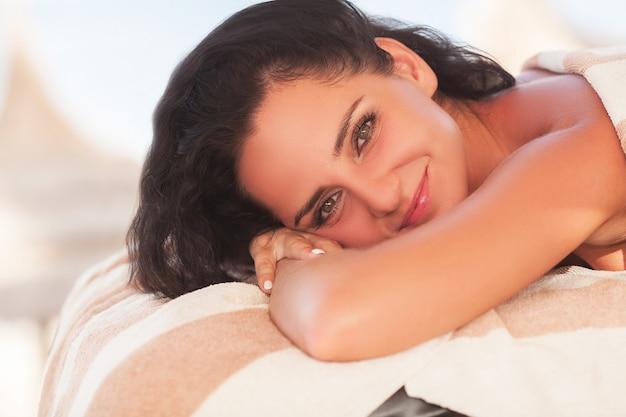 Spa und massage. schöne frau bekommen gesicht und rückenmassage am sonnigen strand. gute qualität.