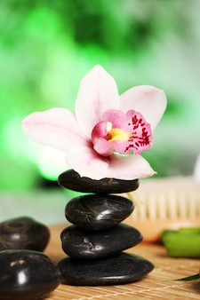 Spa und wellness, massagesteine und blumen auf holztischdecke