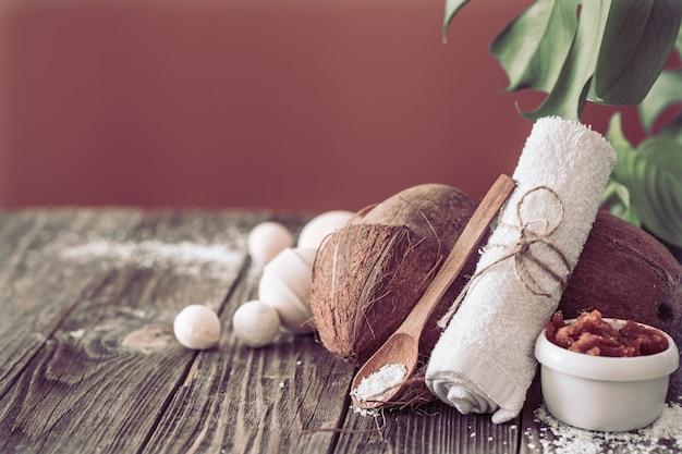 Spa- und wellnessbereich mit blumen und handtüchern. helle komposition auf braunem tisch mit tropischen blumen. platz für text. kokosnuss