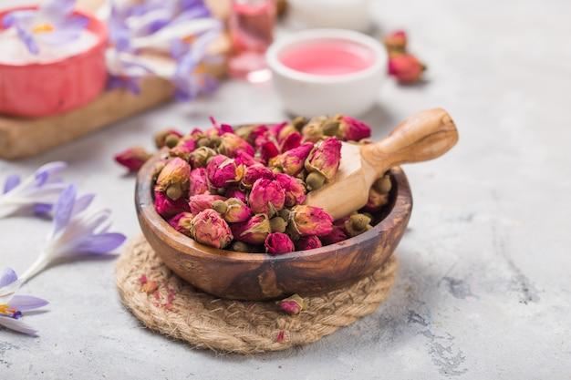 Spa- und wellnesskonzept mit trockenen rosen, rosa öl und milch auf betonhintergrund.