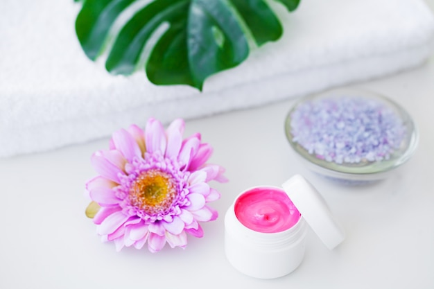 Spa. wellnessprodukte und kosmetik. handtücher, sahne und rosa blumen sorgen für entspannung im spa. naturkosmetik für die gesichtspflege. badeprodukte, badezimmer-set