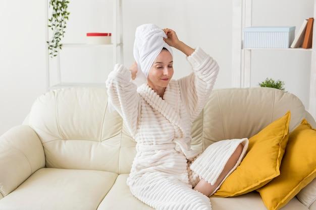 Spa zu hause frau arrangiert ihren bademantel und handtuch