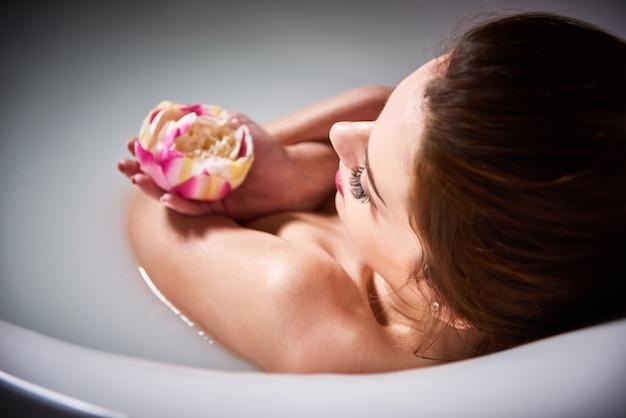 Spa zu hause - frau entspannen im badezimmer. schöne kaukasische frau in der badewanne mit milch. junge frau, die sich um haut kümmert und sich im bad entspannt
