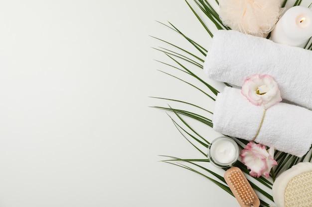 Spa-zubehör und palmenzweig auf weißem hintergrund, kopienraum. körperpflege