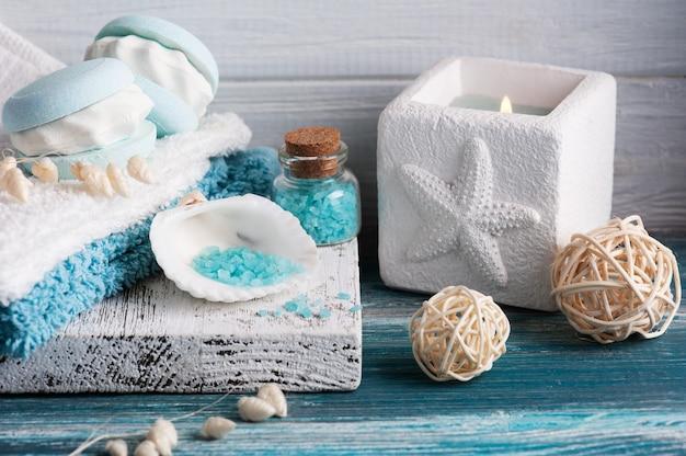 Spa-zusammensetzung mit badebombenmakrone und trockenen blumen auf rustikalem hintergrund. kerzen und salz. schönheitsbehandlung und entspannen