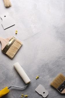 Spachtel zum auftragen von kitt und pinsel und rollen zum malen auf grauem betongrund. ansicht von oben