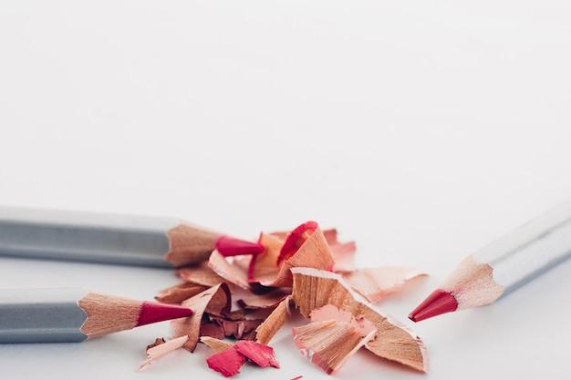 Späne von kosmetischen rosa bleistift und buntstiften auf weiß