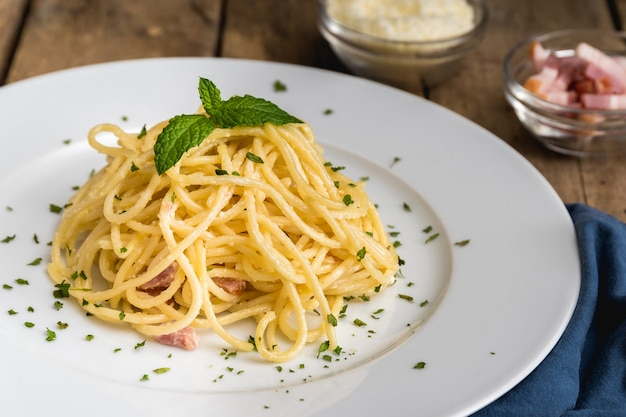 Spaghetti a la carbonara auf einem weißen teller und einem rustikalen tisch