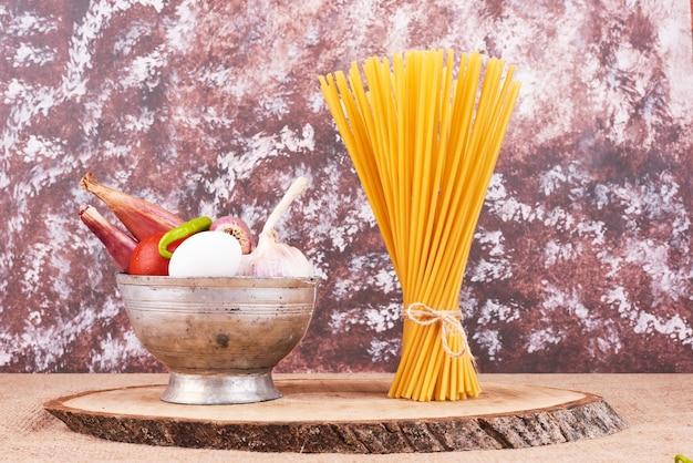 Spaghetti auf einem holzbrett mit zutaten.