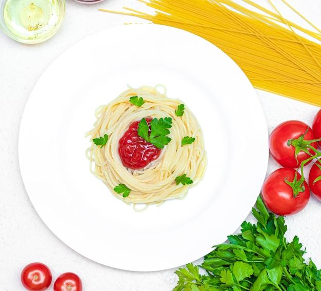 Spaghetti auf einem teller mit ketchup und kräutern. pasta spaghetti mit gemüse ketchup aus gemüse italienisches essen gesundes essen. restaurant food konzept. essen für die speisekarte. vegetarier