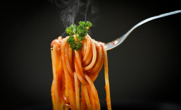Spaghetti auf gabel und schwarzem hintergrund