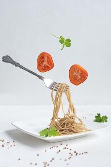 Spaghetti aus buchweizen auf einem weißen tisch.