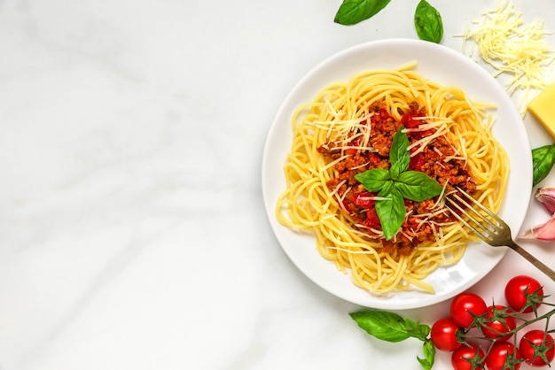 Spaghetti bolognese auf einem weißen teller mit gabel auf weißem marmortisch. gesundes essen. draufsicht