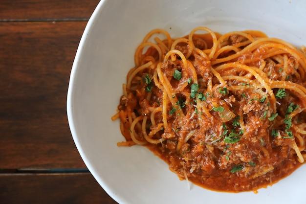 Spaghetti bolognese mit rinderhackfleisch und tomatensauce, garniert mit parmesan und basilikum