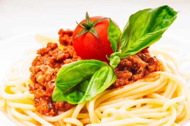 Spaghetti bolognese - nudeln mit tomatensauce und hackfleisch auf weißem teller
