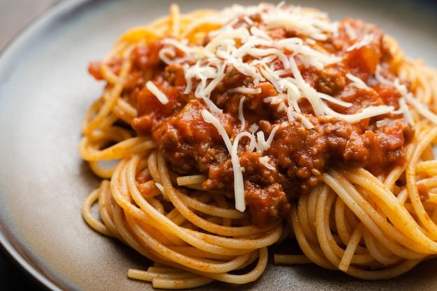 Spaghetti bolognese-sauce oder tomatensauce auf einem dunklen holzbrett