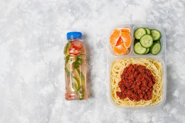 Spaghetti bolognese zum mitnehmen in einer plastikbrotdose mit detoxgetränk und fruchtscheibe auf licht