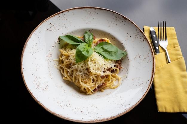Spaghetti carbonara in einem weißen teller auf dem tisch in einem restaurant. hartweizennudeln mit speck, käse und sahnesauce. nahaufnahme