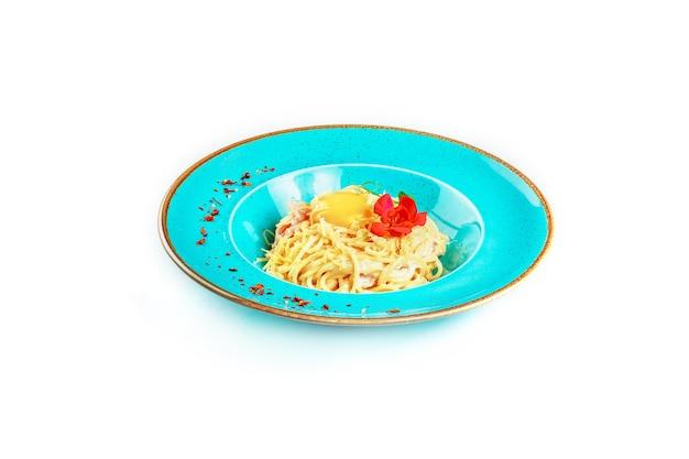 Spaghetti, carbonara nudeln mit parmesan, speck, eigelb auf einem weißen teller. italienische küche. isoliert.