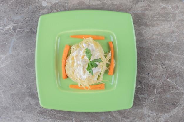Spaghetti, fein gehackte karotten und grüns auf dem teller, auf dem marmor.