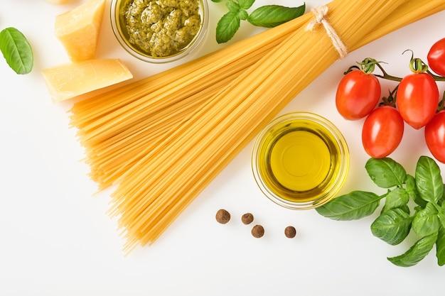 Spaghetti, frische tomaten, kräuter und gewürze. zusammensetzung von gesunden lebensmittelzutaten isoliert auf weißem hintergrund, ansicht von oben